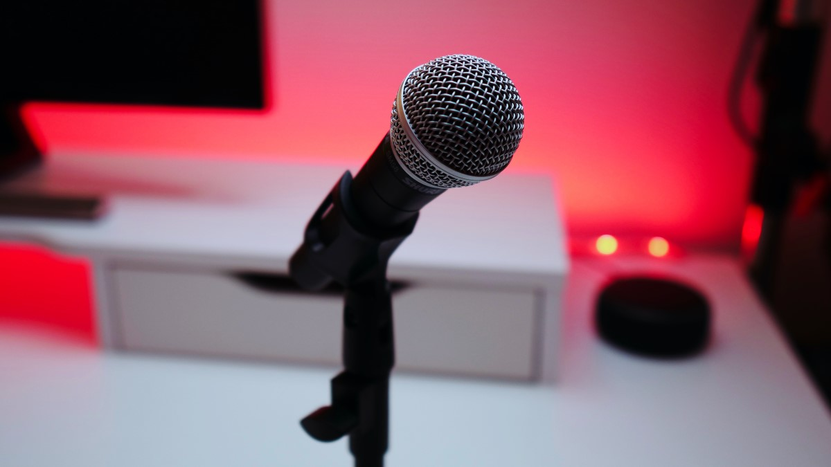 black and grey microphone in front of screen and desk with red lighting
