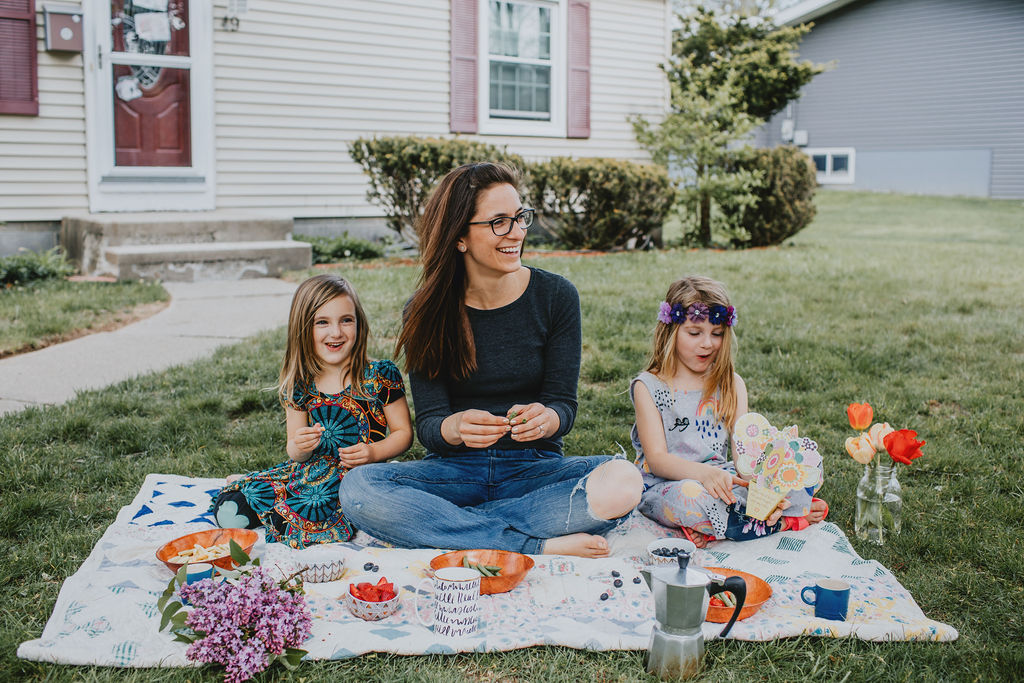 Laura with two daughter on a picnic blanket outside eaching fruit