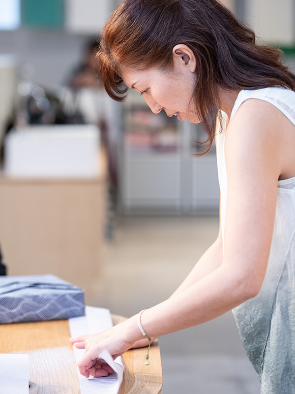 Shiho folding paper on a wooden table.