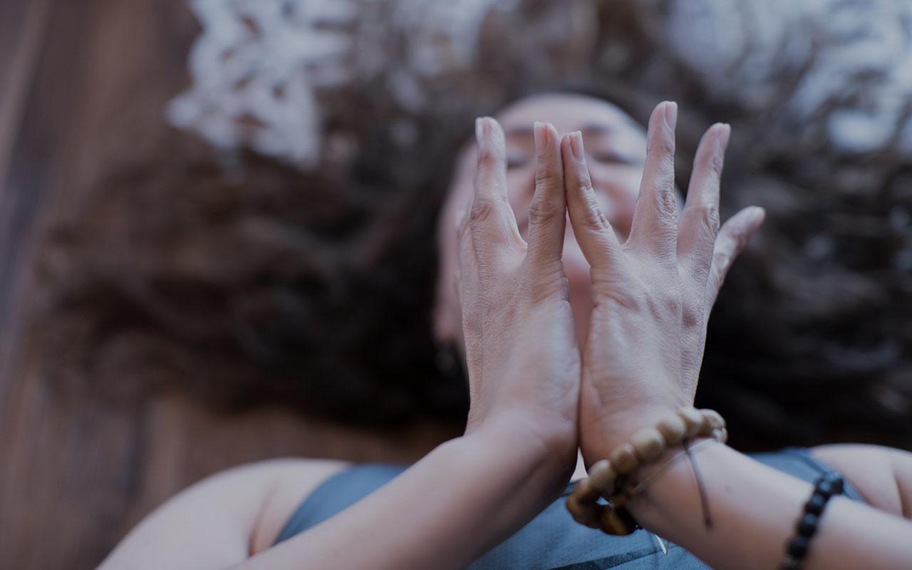 Mujer medita y practica yoga en el piso, con sus dos manos abiertas.