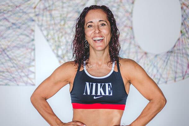 Mujer sonríe con un top deportivo de Nike.