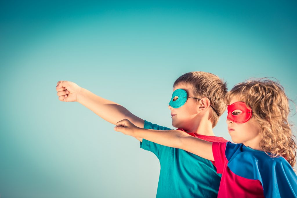 2 children wearing super hero masks and capes with their arms up like they