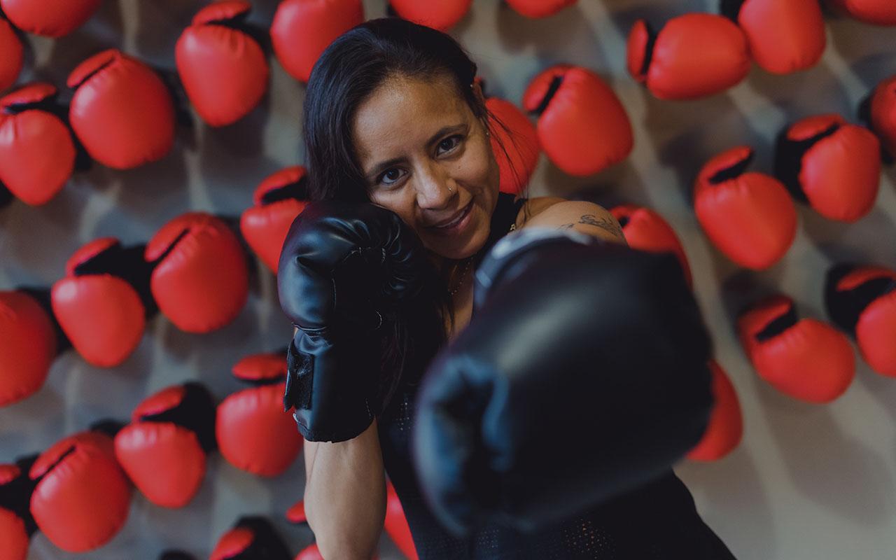 Mujer con guantes de box hace movimientos de boxeo