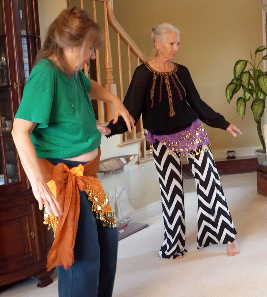 mature senior women wearing hip scarfs learning to belly dance in living room