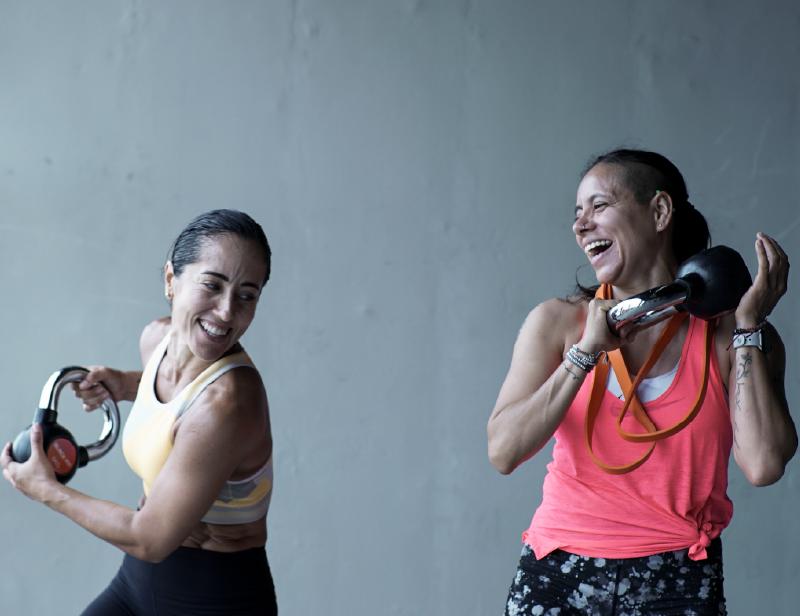 Dos mujeres con ropa deportiva y sonrientes entrenan con kettlebells en la mano.