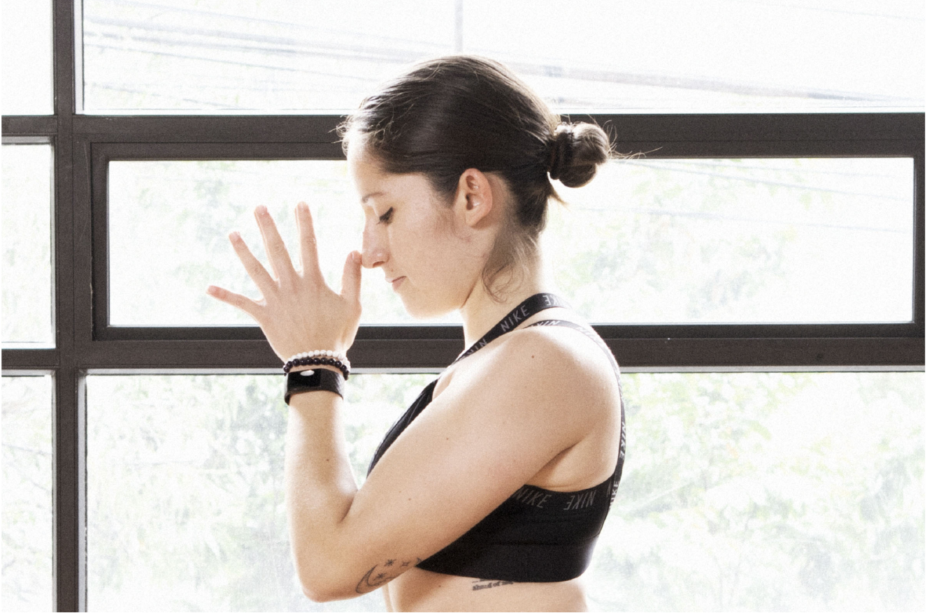 mujer meditando al frente de una ventana con las manos en la cara
