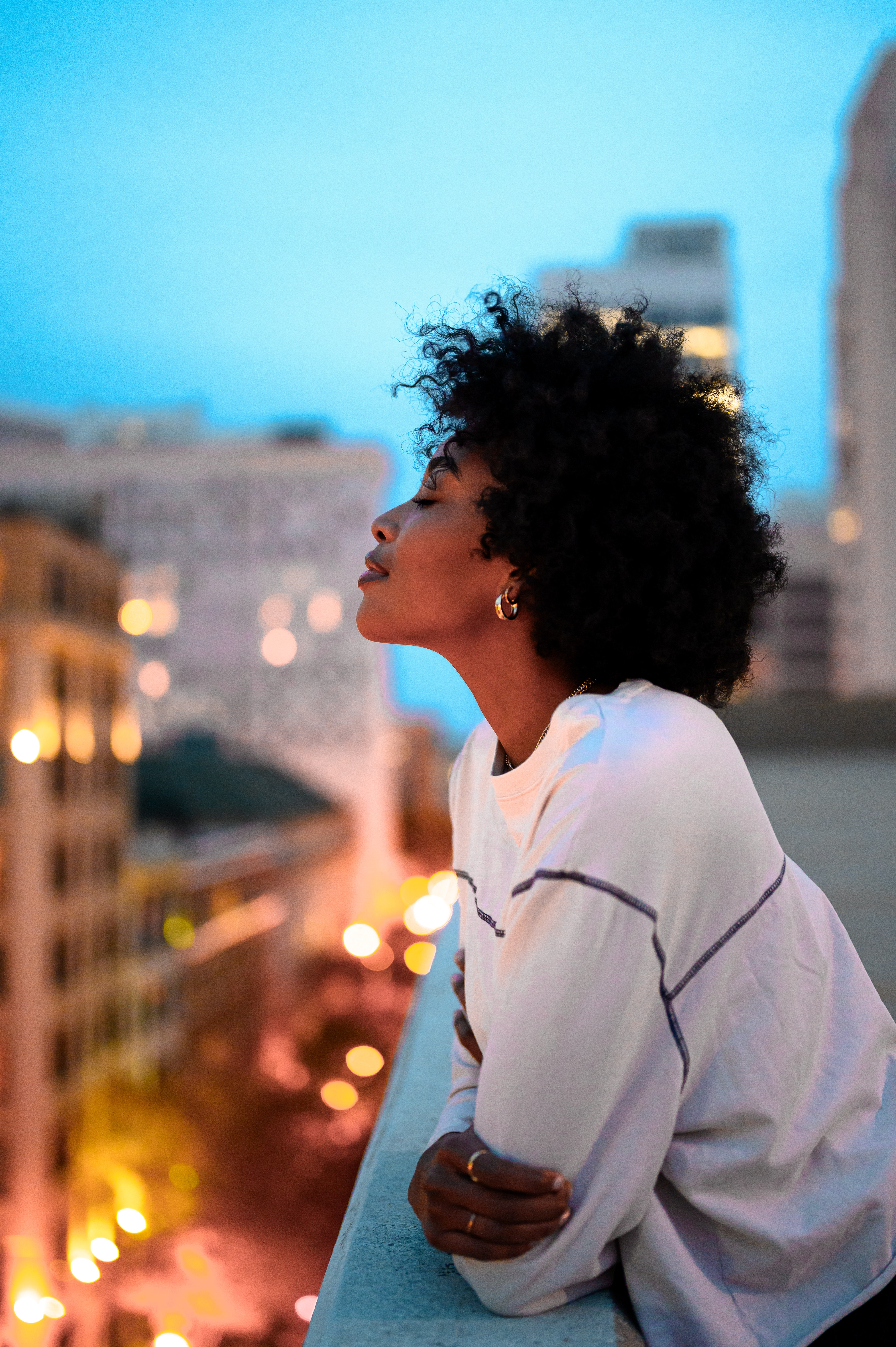 black woman with closed eyes leans against a balcony railing with evening city scene in background