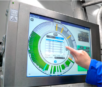 Persona controla rotativa de ordeño desde panel de control táctil DeLaval.