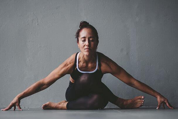 Mujer medita en una postura de estiramiento y calma.