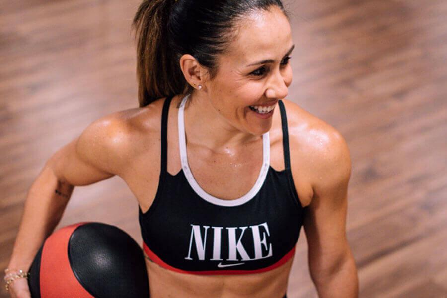 Mujer sonriente con un top de Nike agarra una pelota medicinal y se prepara para entrenar