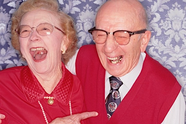 A man and woman both dressed in bright red roaring with laughter