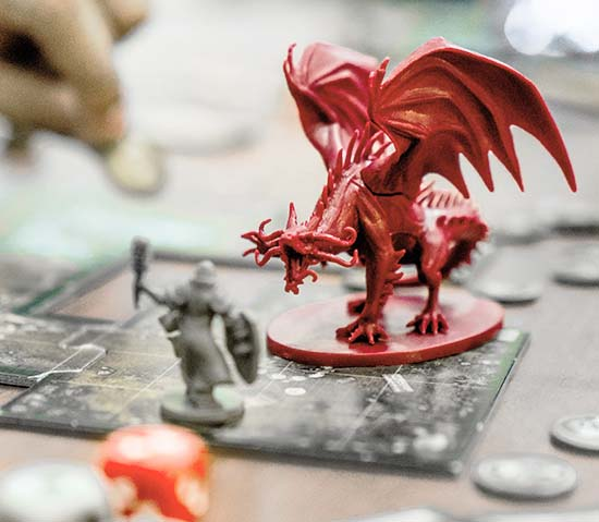 A cleric figurine stating in front of a red dragon on a gameboard of a tabletop fantasy roleplaying game