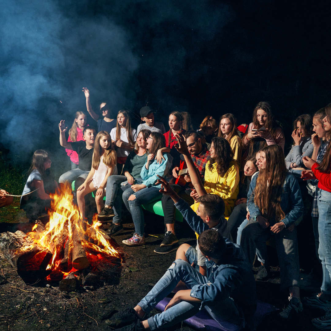 crowd of young people sing around a campfire