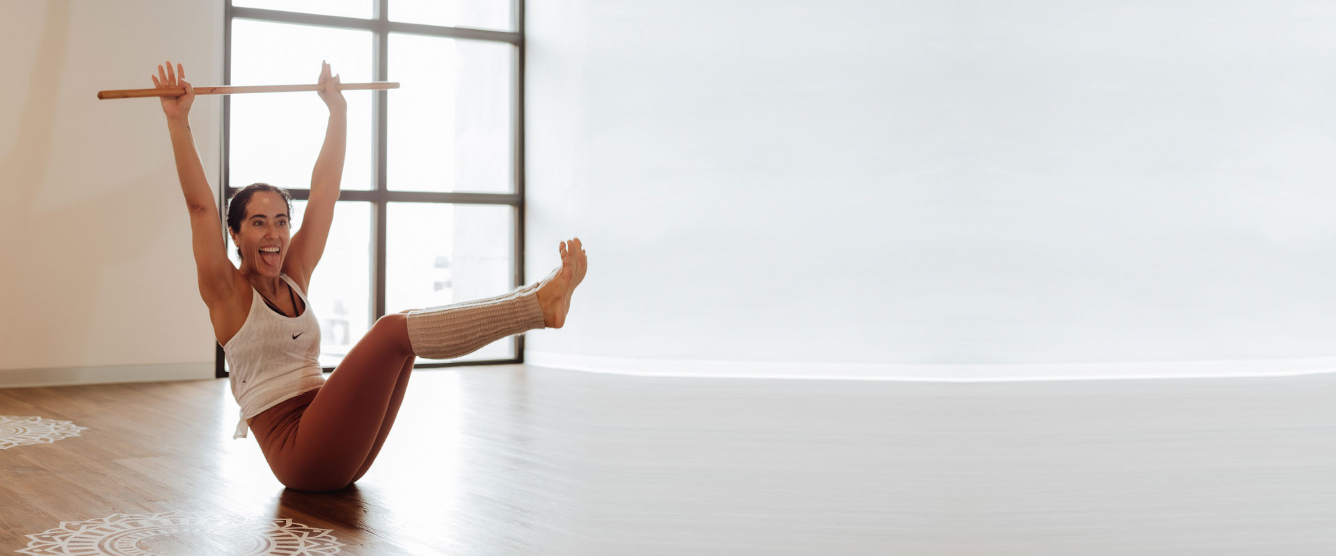 Mujer saca la lengua mientras practica yoga en una postura de bote en una studio de yoga.