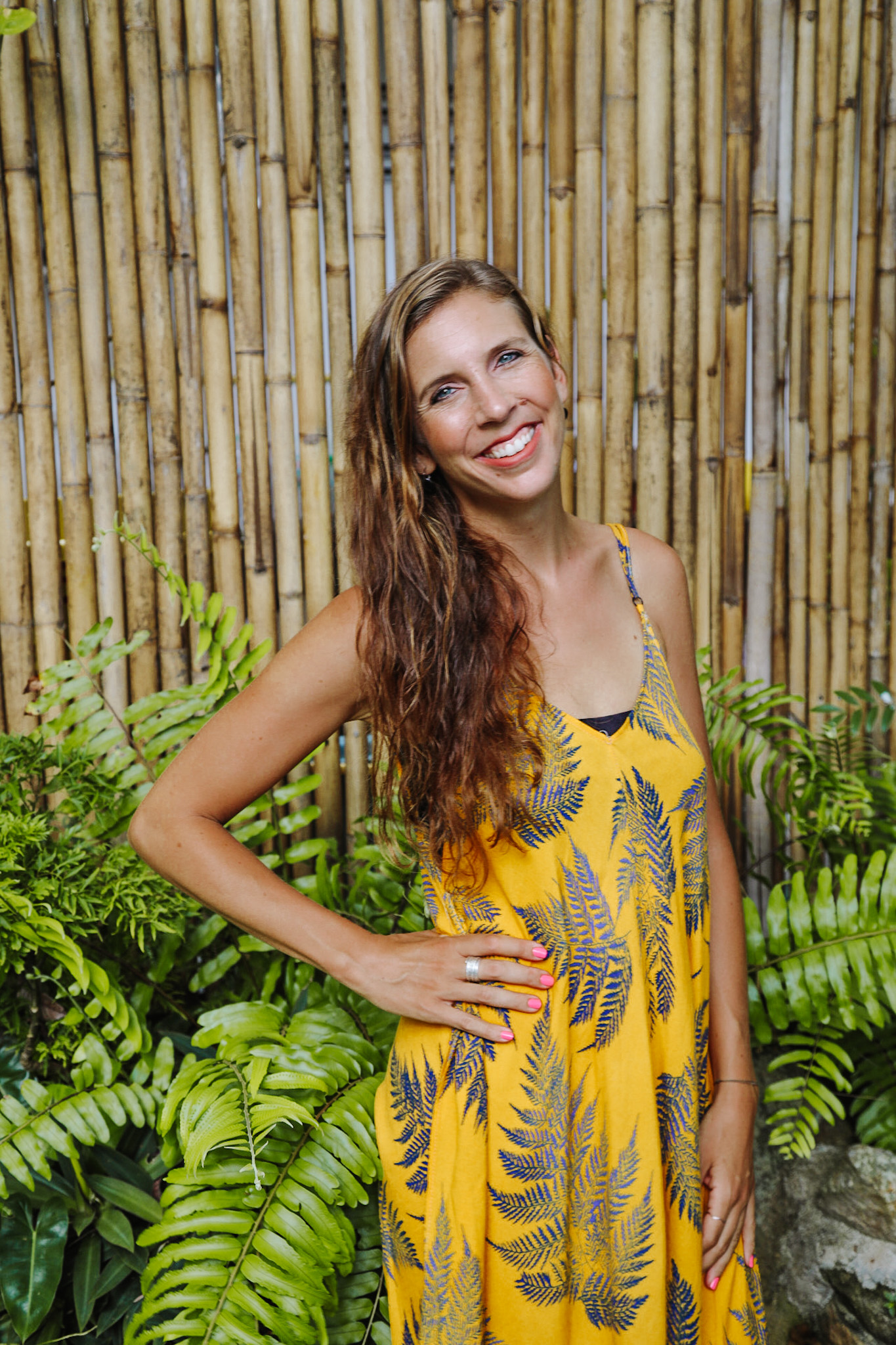 Woman smiling at the camera in front of a bamboo stick wall