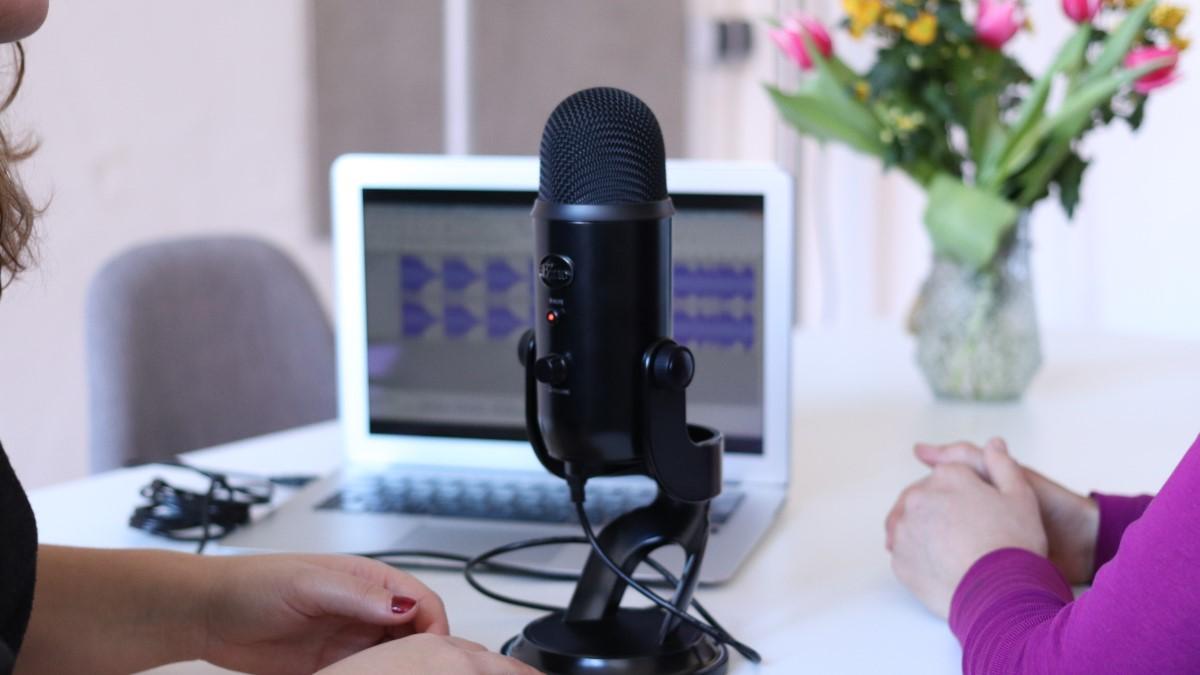 black microphone inbetween 2 females with laptop and flowers behind