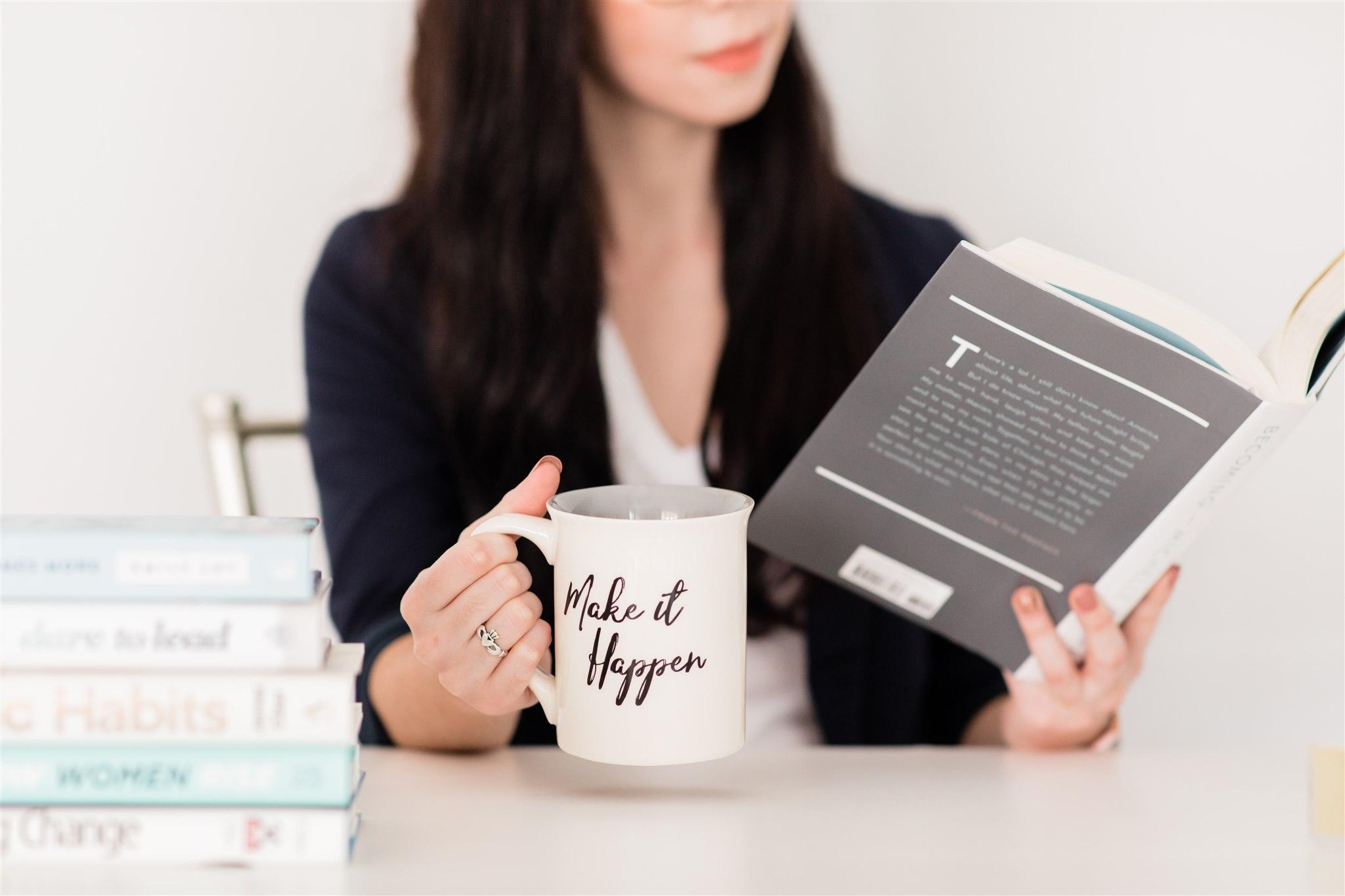 Woman reading and holding mug