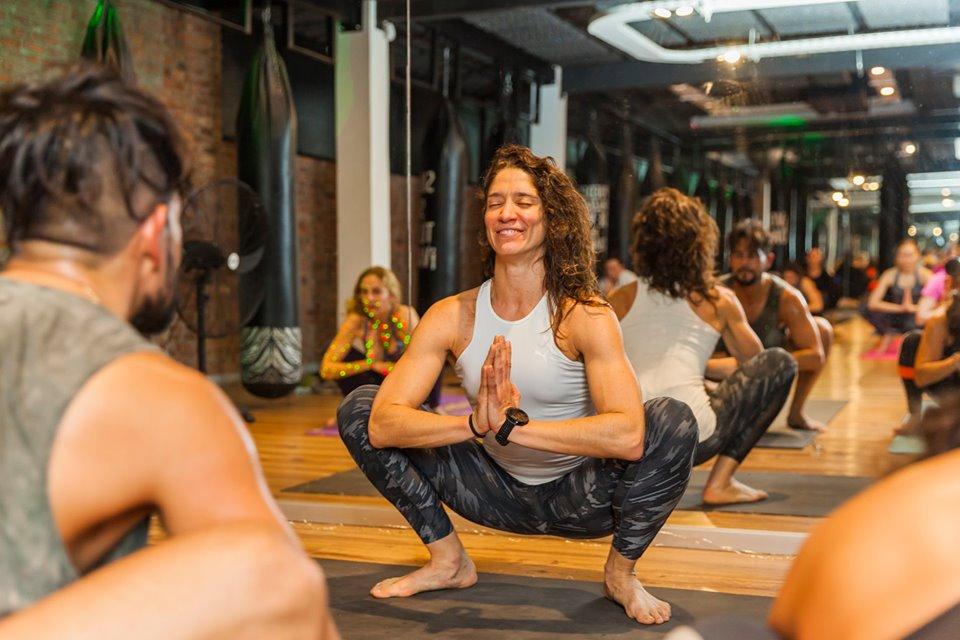 Mujer sonriente practica yoga en una postura calma y en paz.