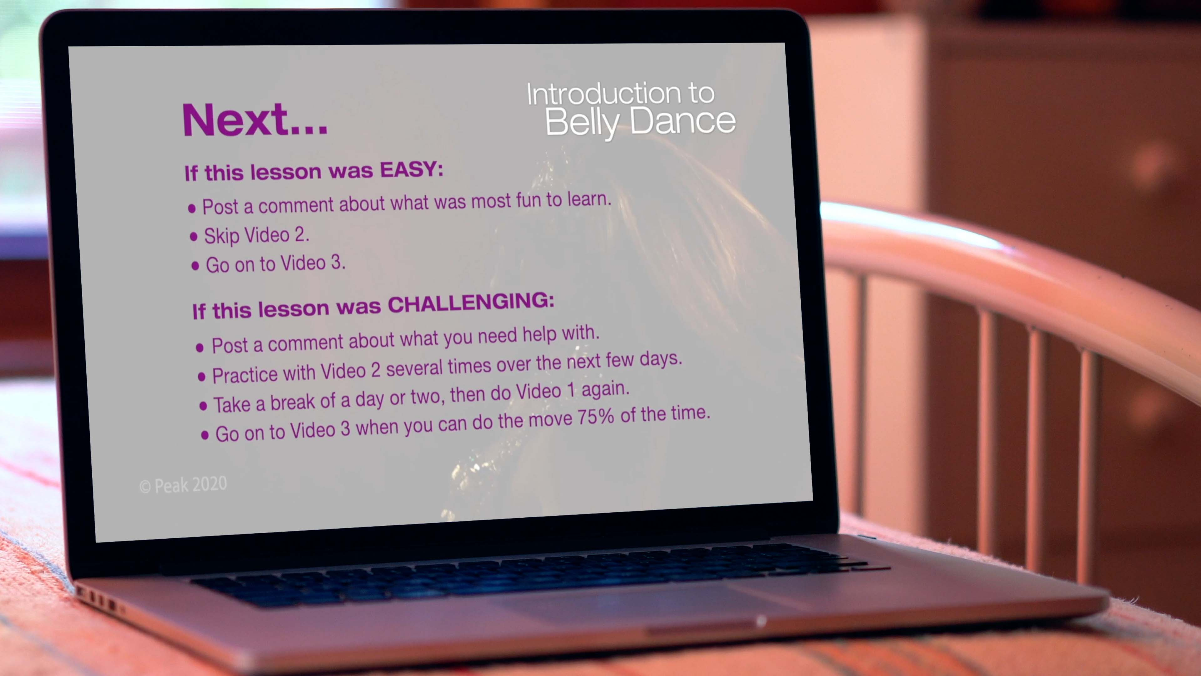 laptop computer on bed showing online belly dance course on screen