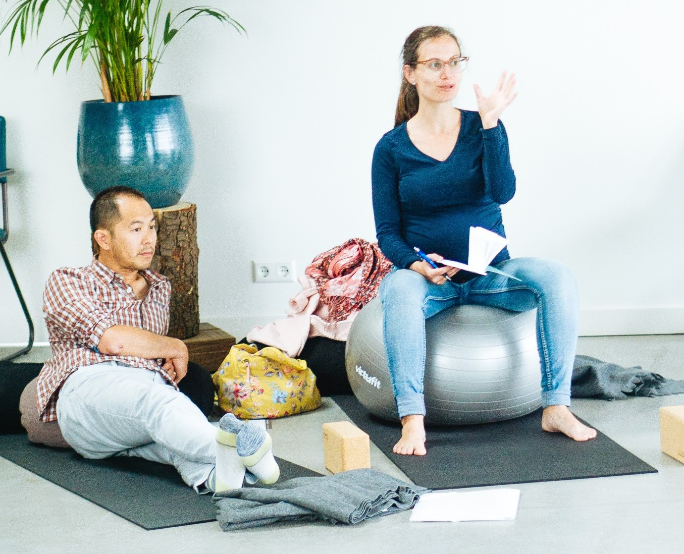 pregnant woman sitting on gymnastics ball talking and gesturing