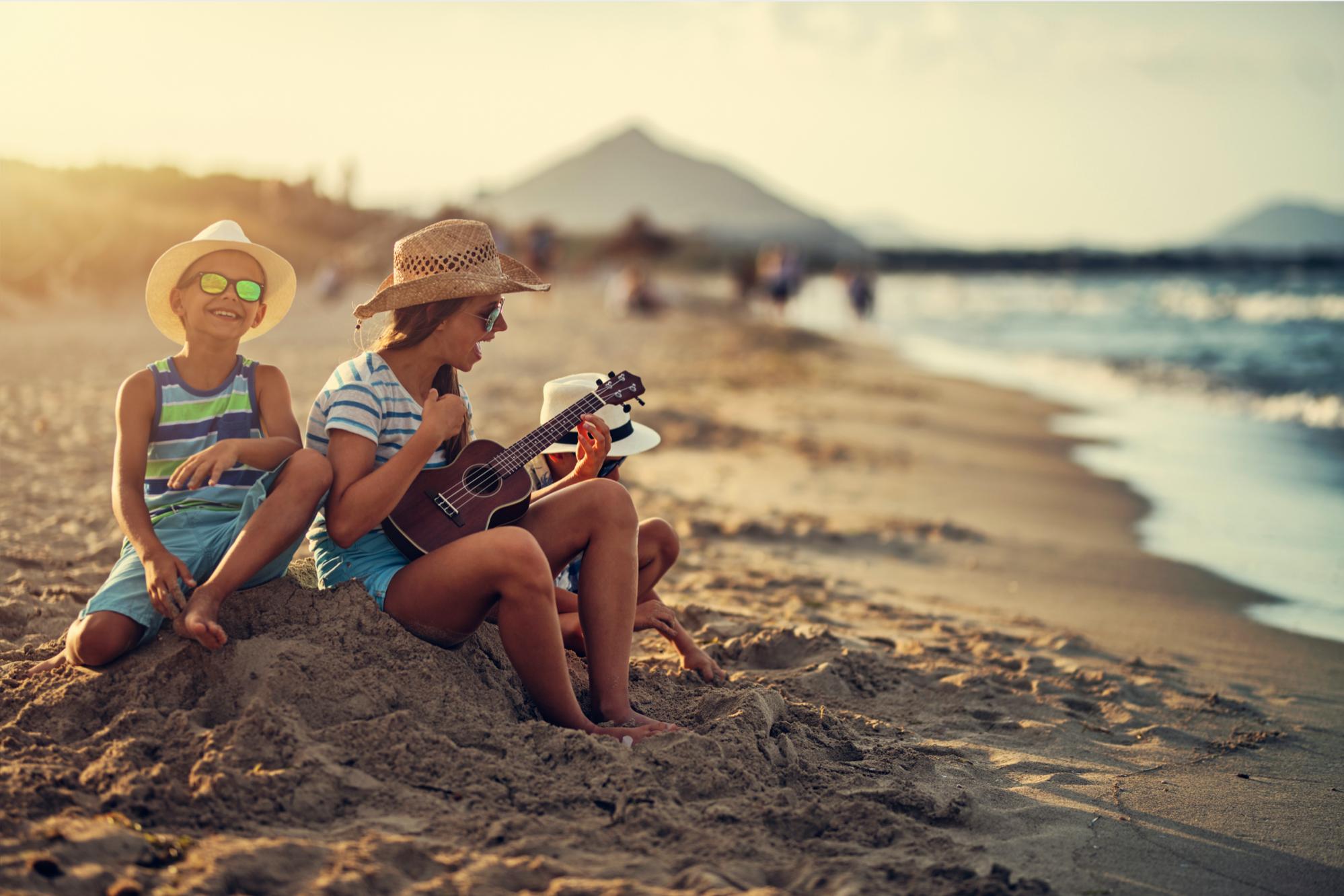 family group on beach play ukulele