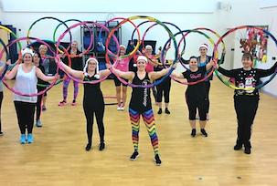 Class members taking a fitness hoop class