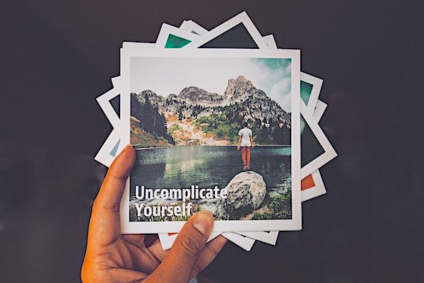Hand holding a pile of photographs with the words 'Uncomplicate Yourself' written on the top one