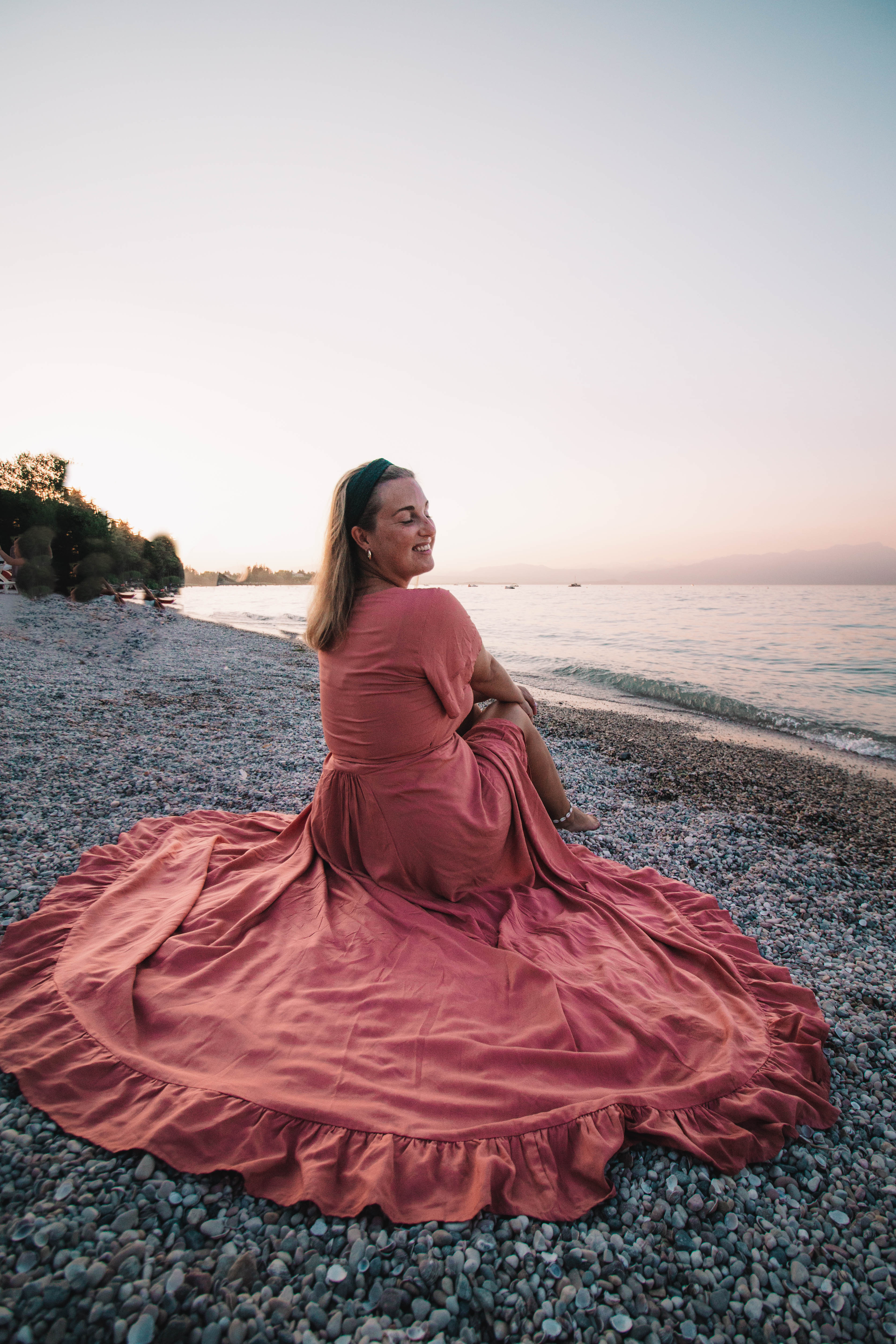 girl in pink flowy dress by the Garda Lake in Italy