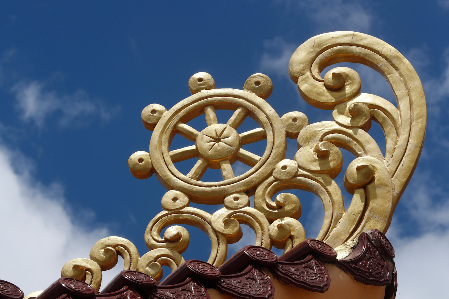 Golden painted Dhamma Wheel set against the sky