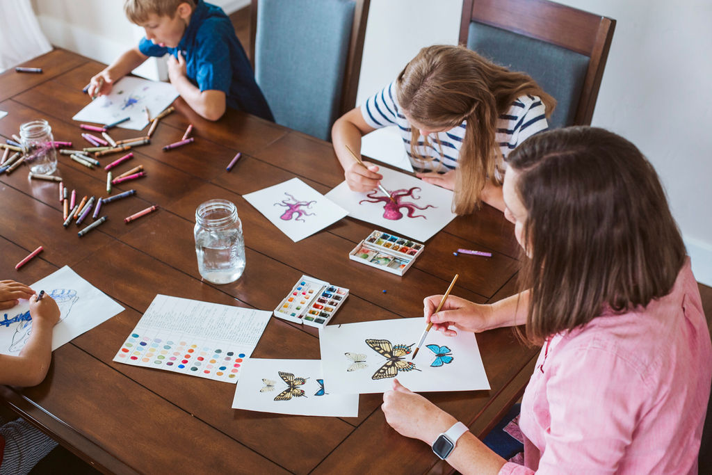 Mother and children sitting at kitchen table coloring and watercolor painting nature images
