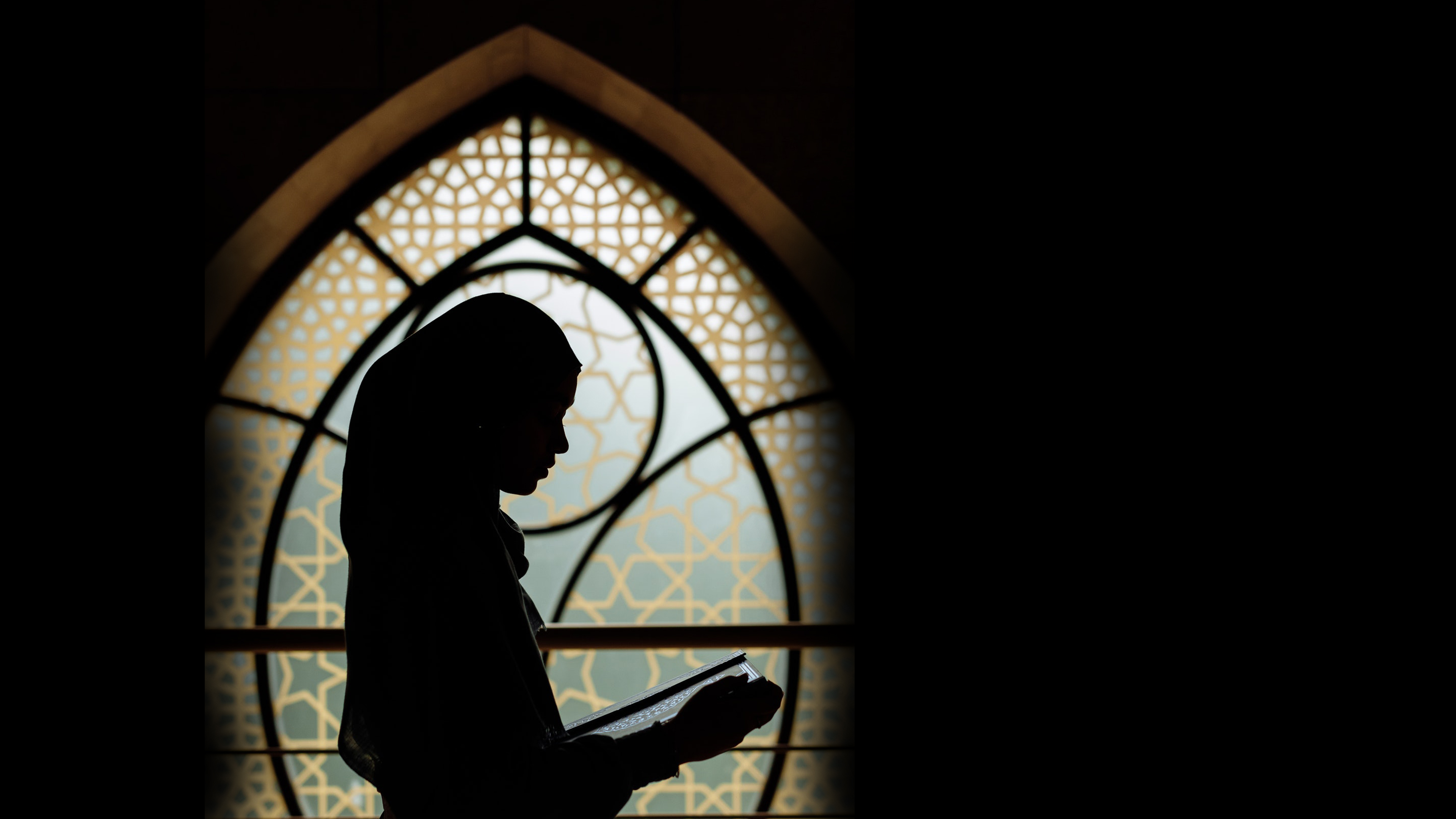 silhouette of Muslim woman reading in the masjid