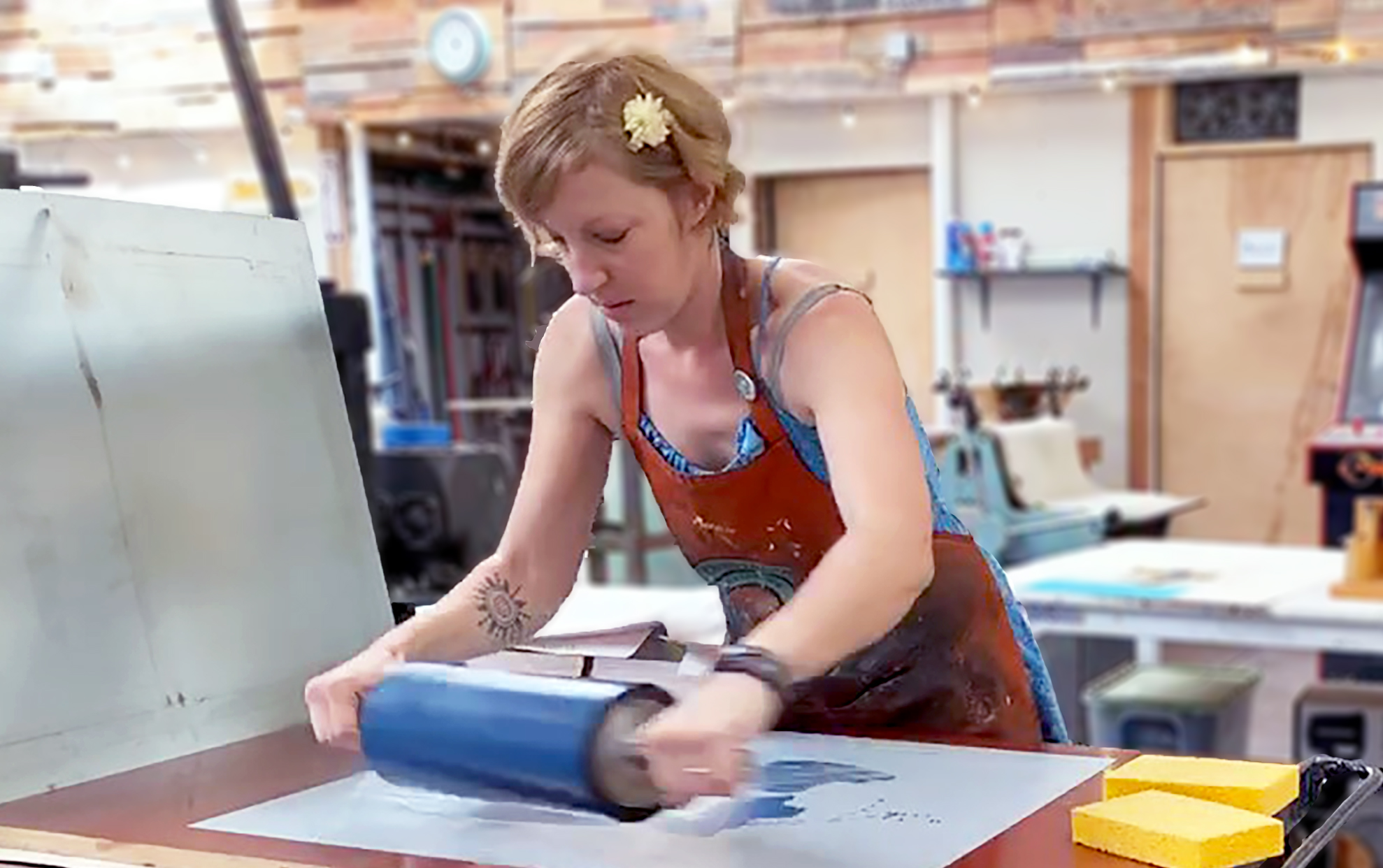 Dana printing a fine art lithograph with the printmaking press