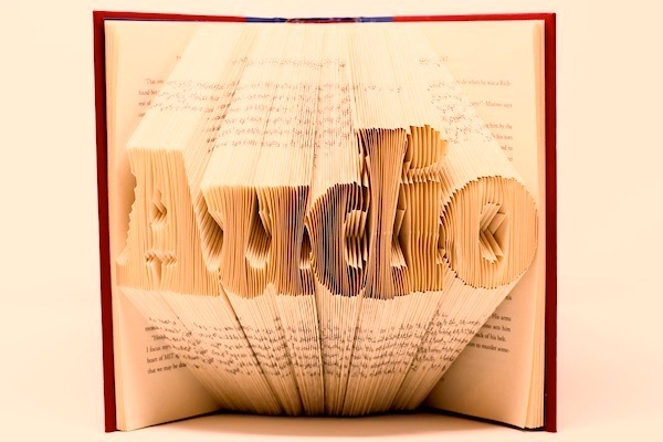 A paper book standing open with its pages folded in such a way that the word
