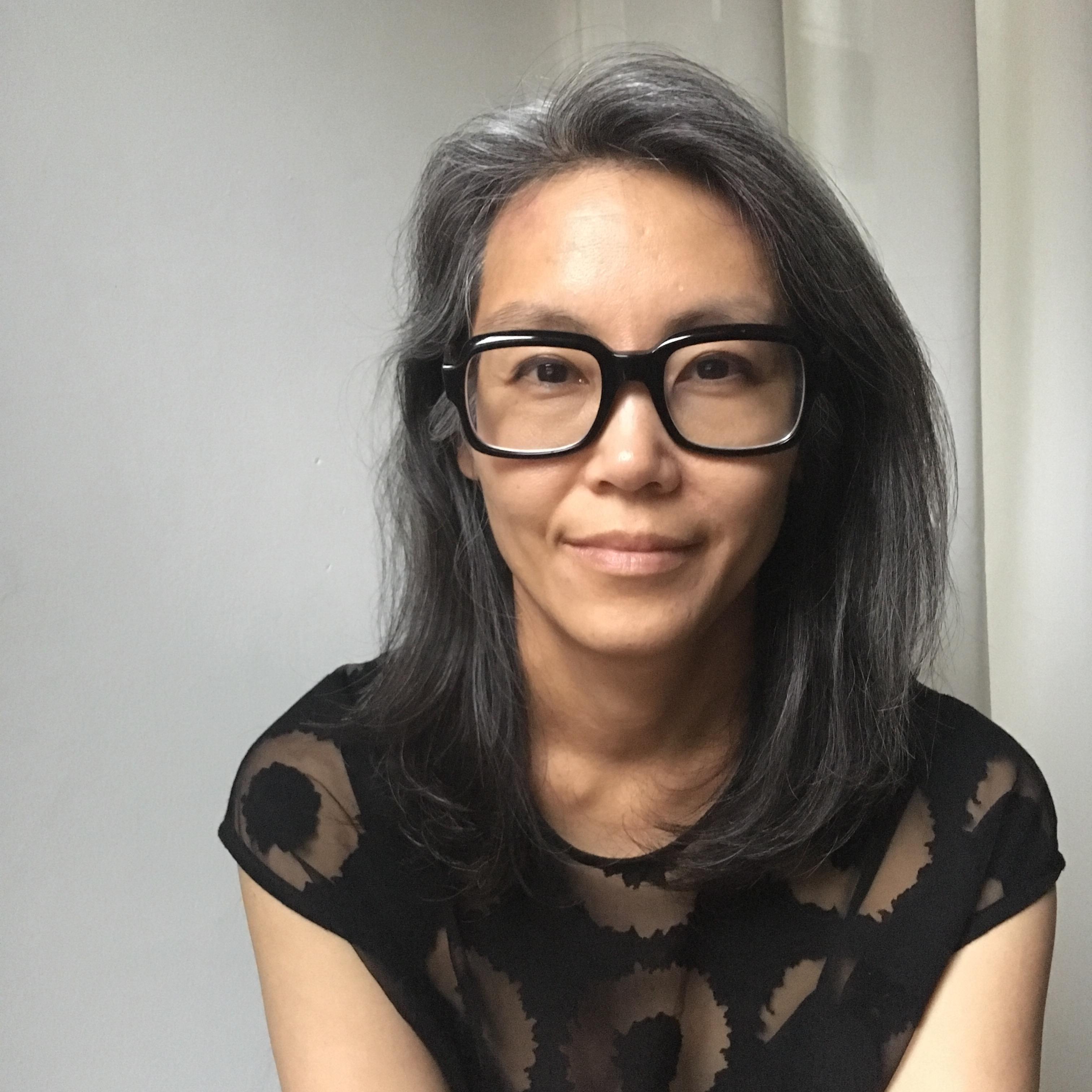 Headshot of Kay Takeda with black glasses and black shirt on.