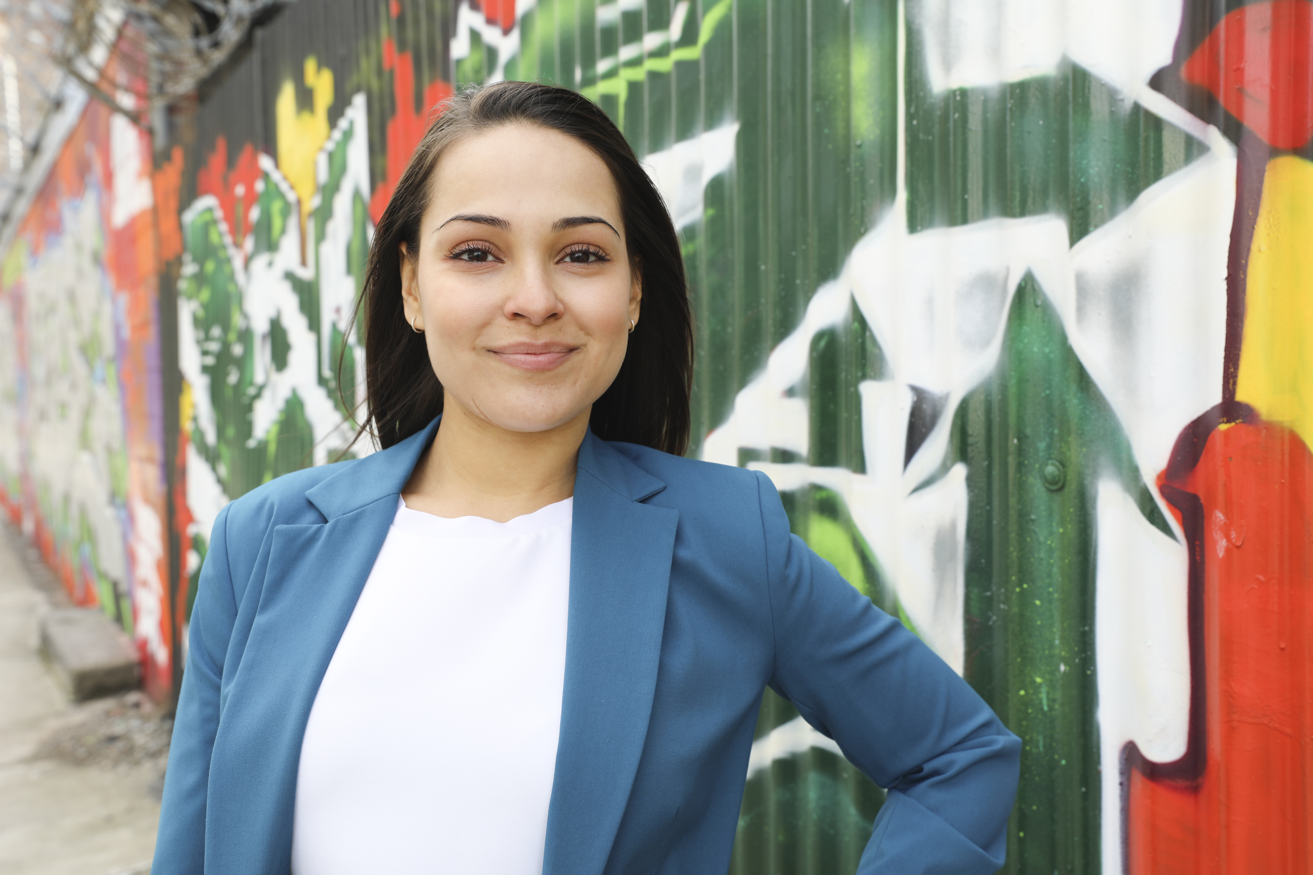Image of Yanely Espinal in front of a wall of graffiti. She is wearing a blue blazer and white shirt.
