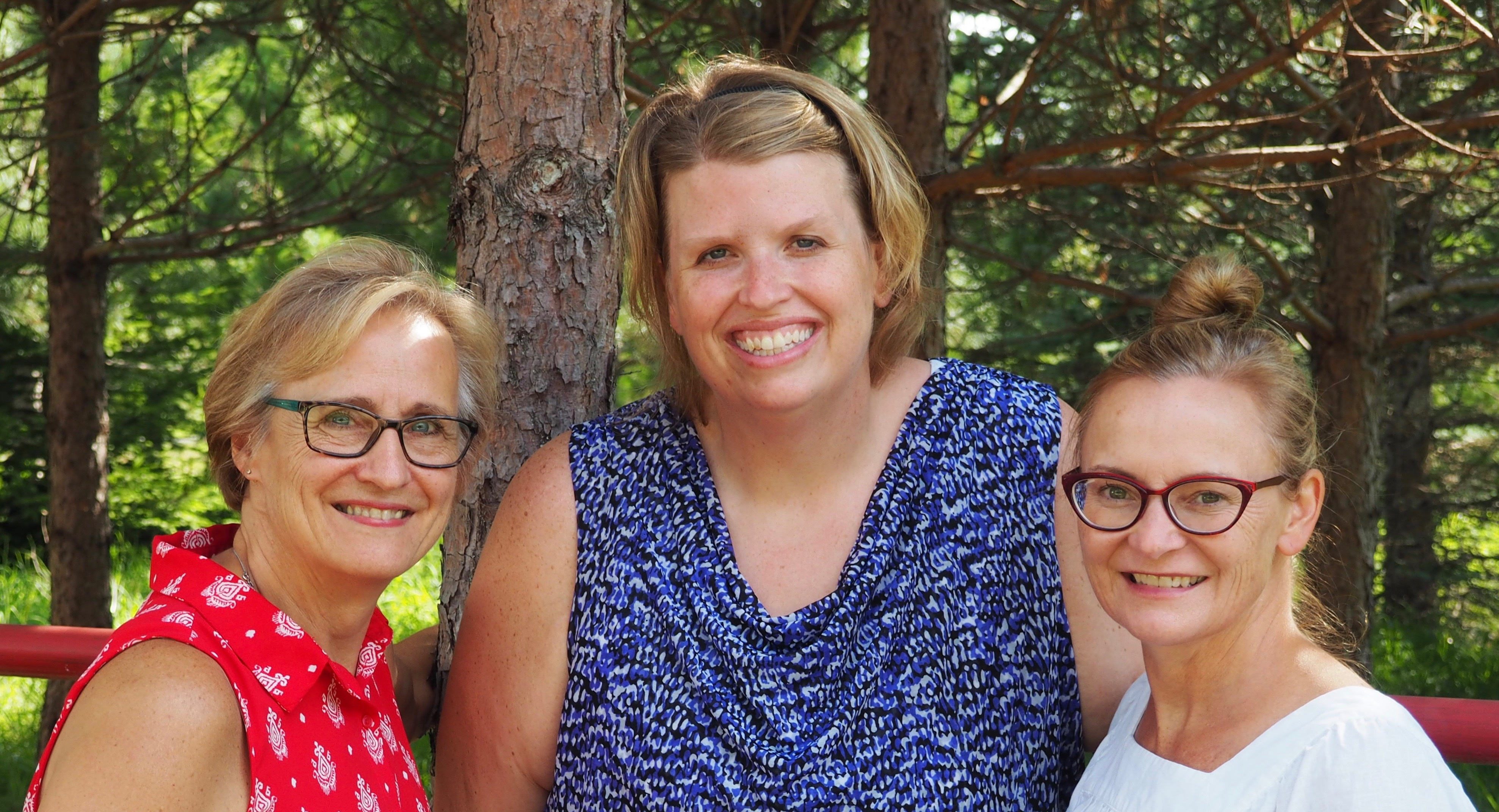 three women standing by a pine tree