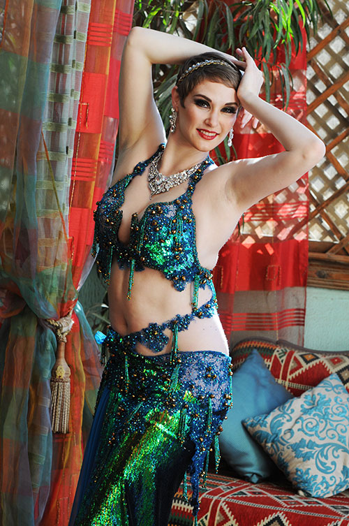 Belly dancer in a teal costume on a background of red curtains and latticework.