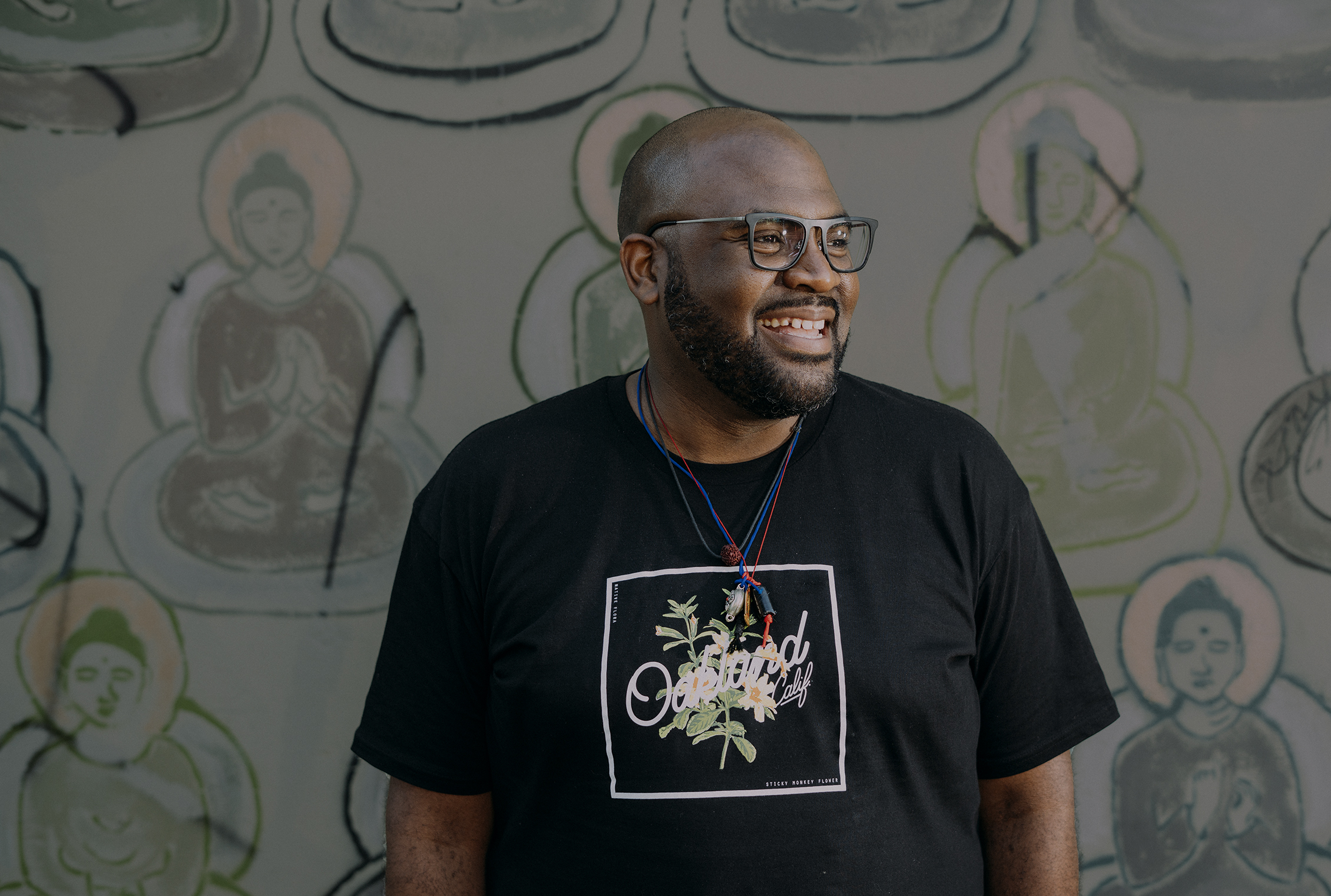 A photo of Lama Rod Owens in front of a wall with buddhas painted on it