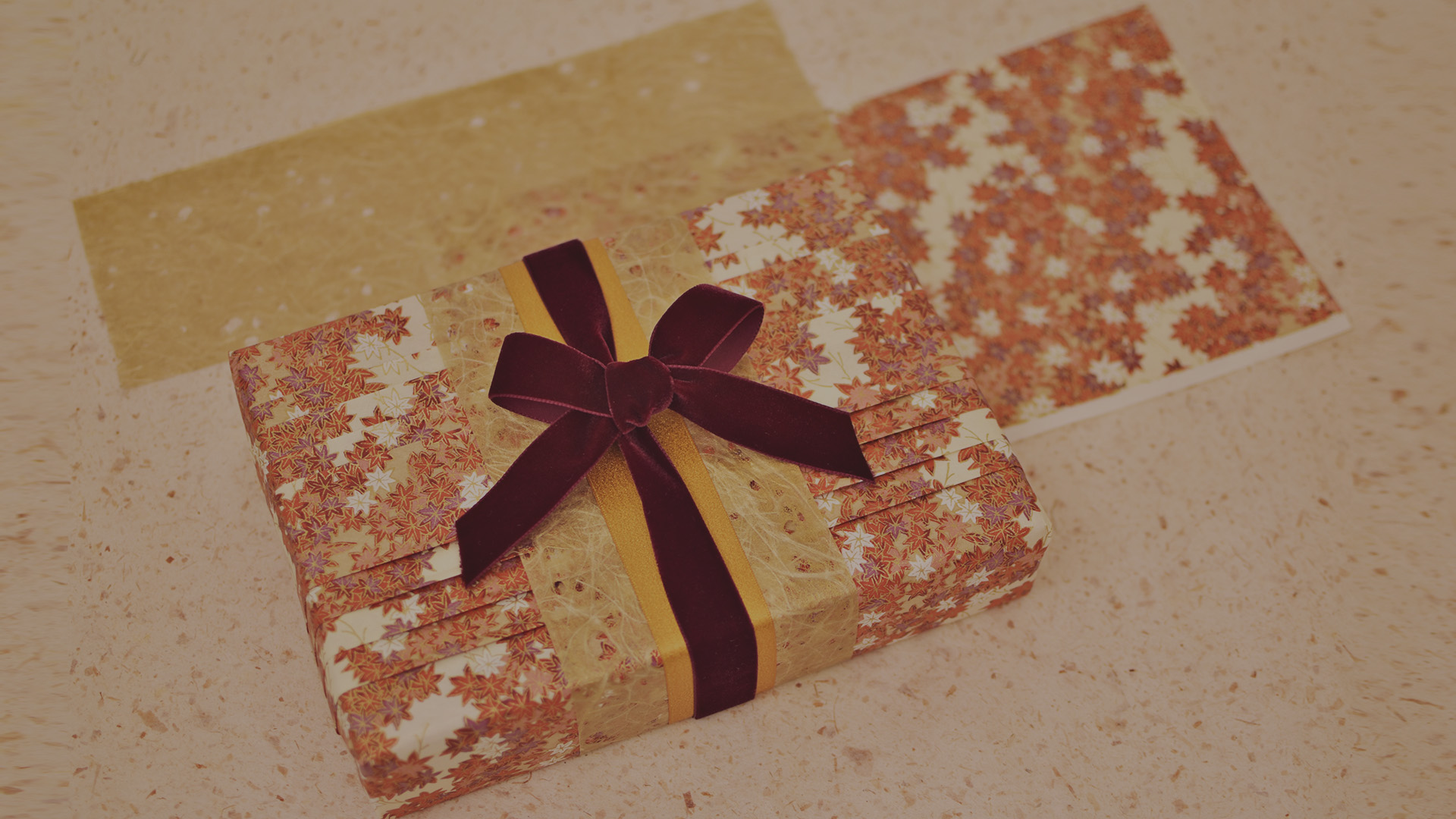 Gift wrapped in a paper with floral pattern an pink flowers as decoration.