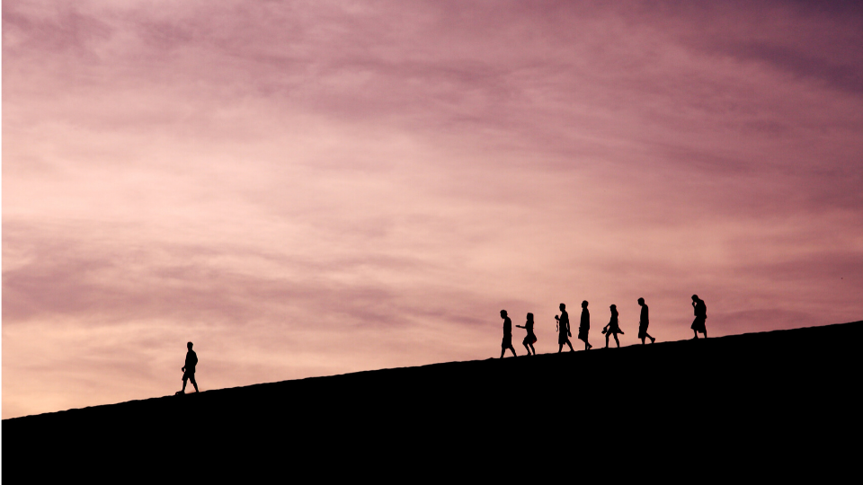 Sunset people walking on a hill