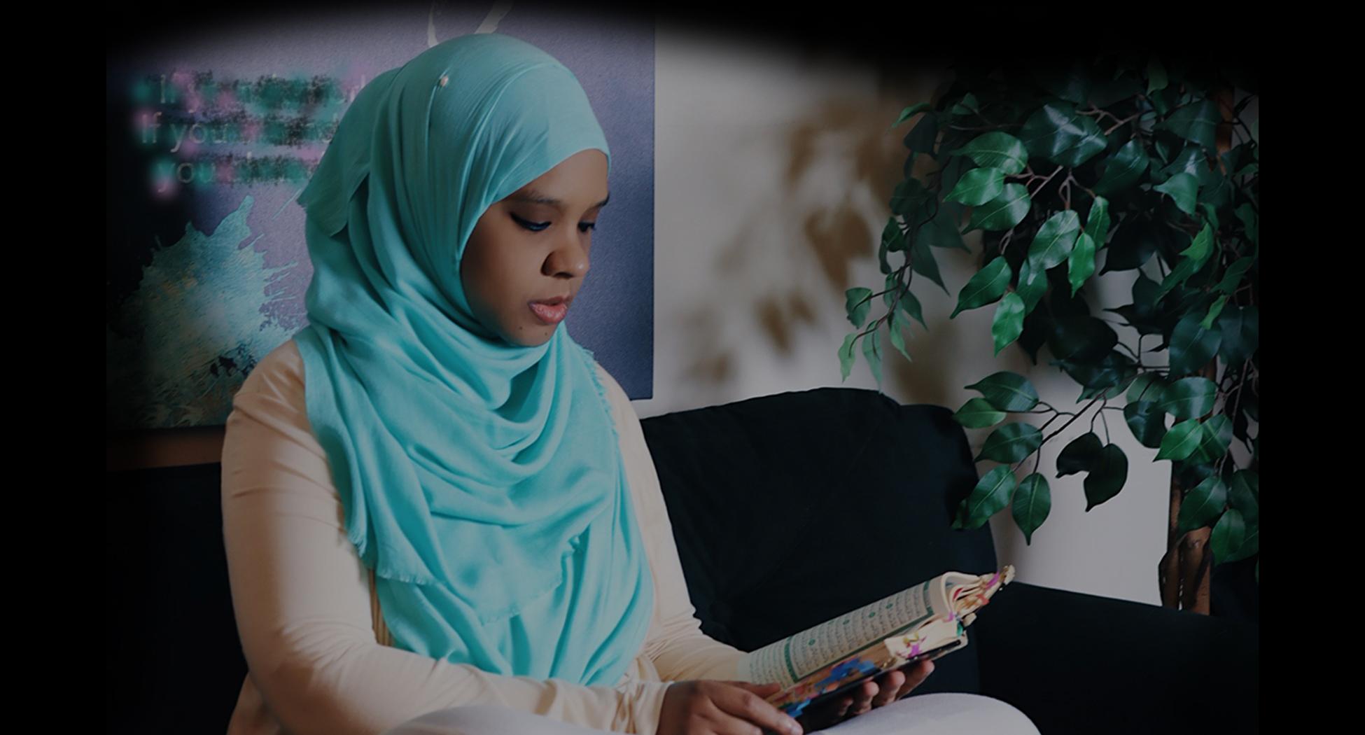 Photo of Umm Zakiyyah in turquoise hijab reading Qur