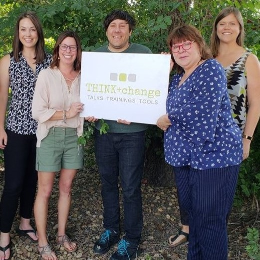 THINK+change team smiling and holding a THIKN+change sign. Pictured are 4 women and 1 man.