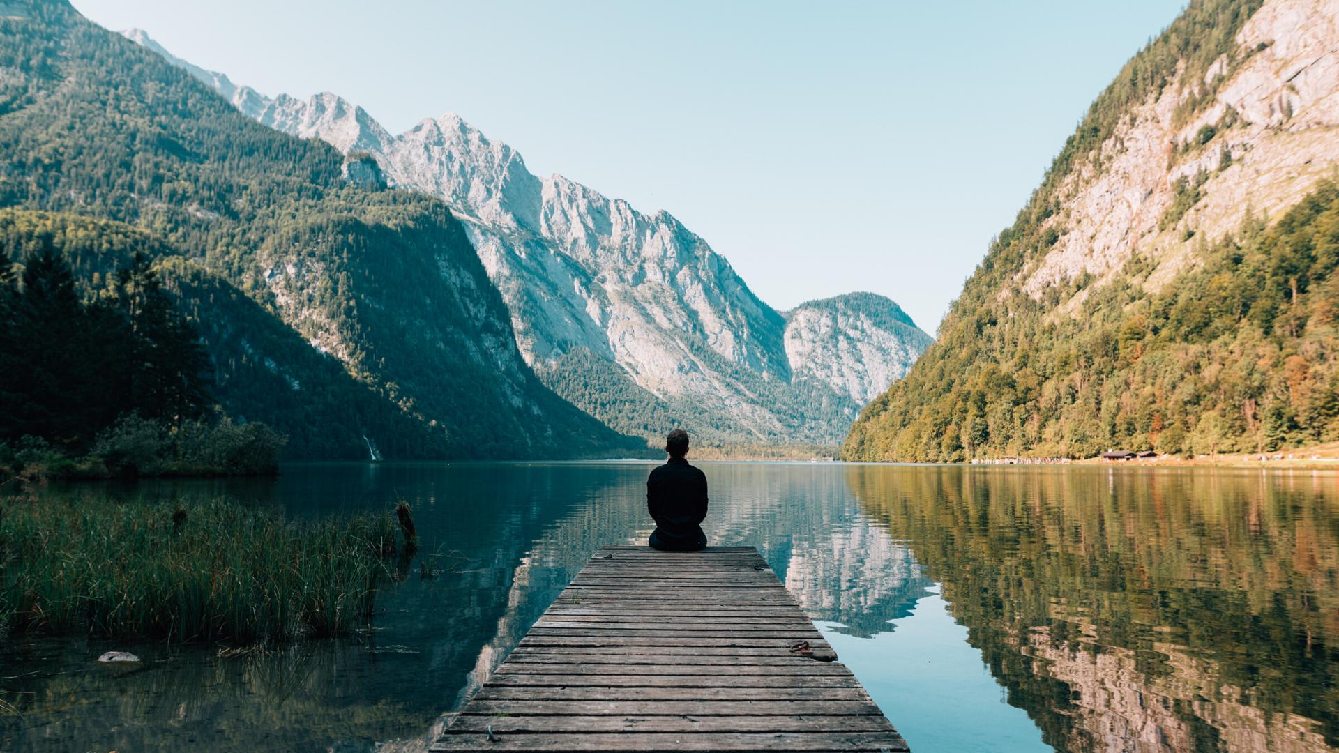 Person på brygga vid sjö och berg