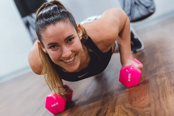 Mujer sonriente entrena y hace deporte con dos mancuernas.