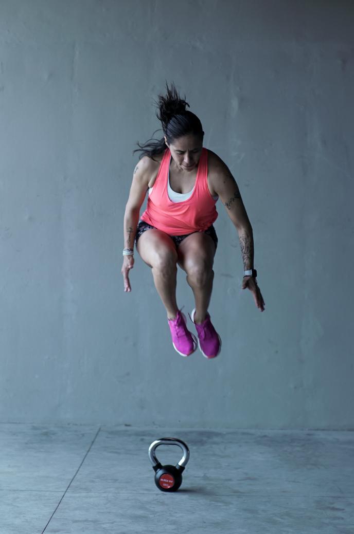 Mujer en ropa deportiva salta y hace ejercicios al lado de un kettlebell.
