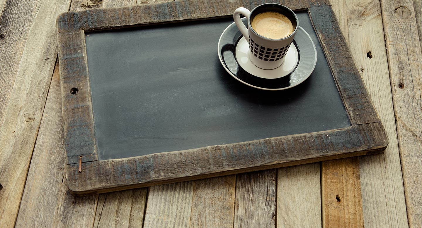 A chalkboard with a cup of coffee