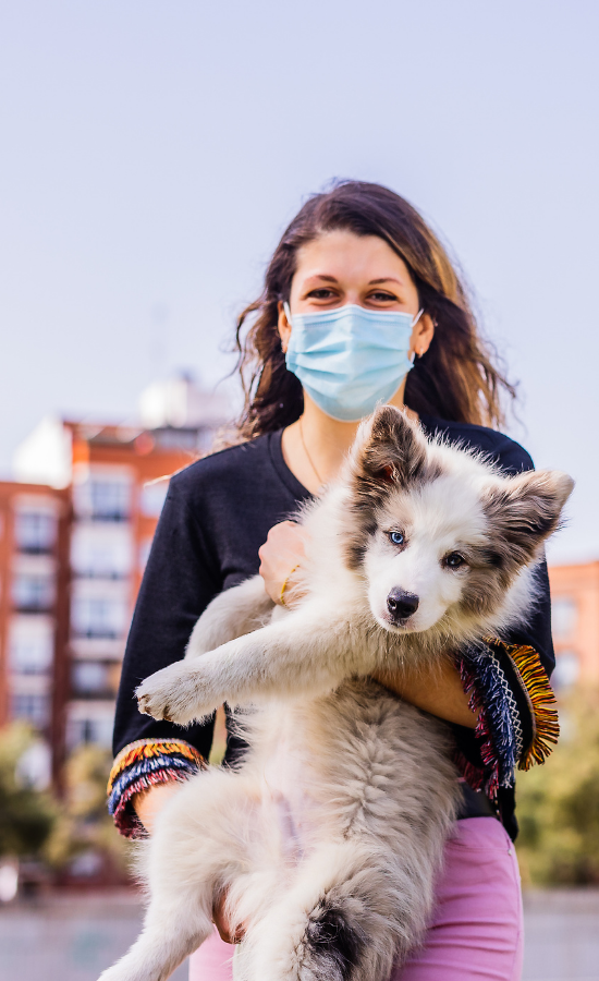 woman in mask holding her fluffy puppy
