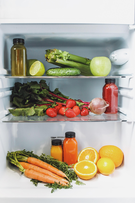 refrigeradora, limones, manzanas, zanahorias, fresas, zanahorias, naranjas, botellas de jugos.