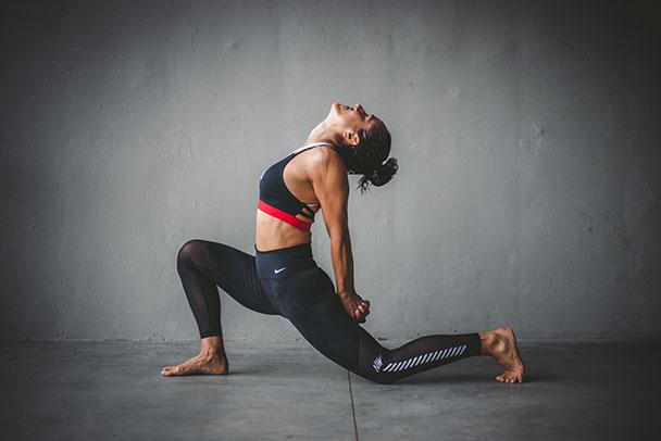 Mujer practica yoga y estiramiento sobre concreto.
