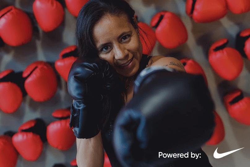 Mujer con guantes de box practica movimientos de boxeo